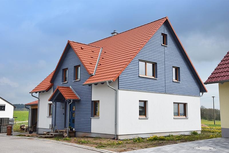 Holzhaus mit Holzschalung und Carport